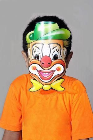 A kindergarten kid wearing a clown mask photo