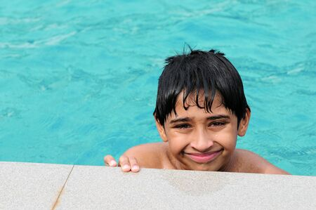 A handsome Indian kid playing in the pool photo