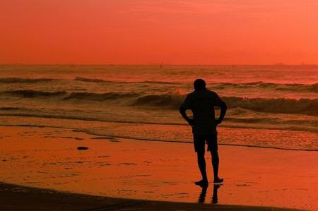 a young man standing at the ocean during sunrisesunset photo