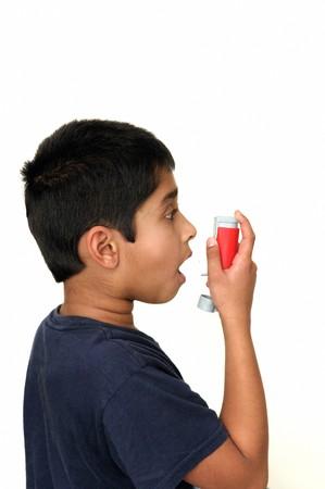 inhaler: An handsome young Indian child using the inhaler