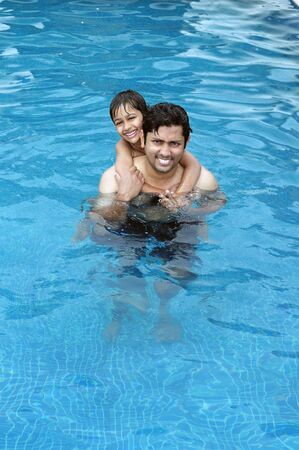Father and Son having fun in the swimming pool