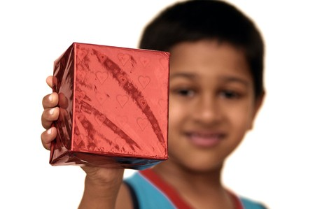 An yound Indian kid holding a gift for you