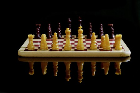 Chess board and coins isolated on a black background
