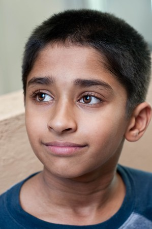 An adorable young Indian boy day dreaming