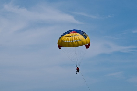 Paraglider launching from the ridge with colorful canopy against a blue sky. photo