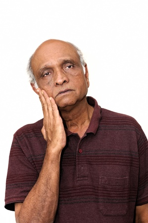 A senior Indian man looking very sad