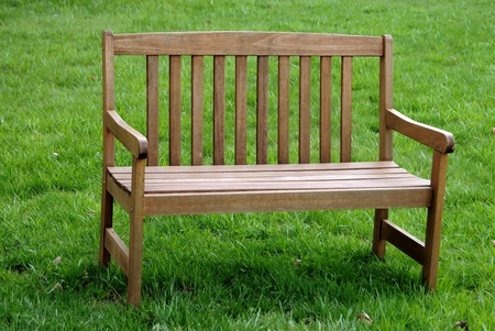 old furniture: An empty park bench isolated against the grass background Stock Photo