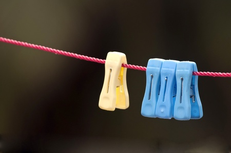 clench: Colorful clip hanging on a cord used for drying cloths Stock Photo