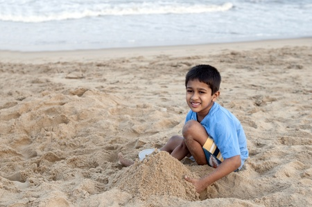 an handsome young indian kid building sand castle at the beach photo
