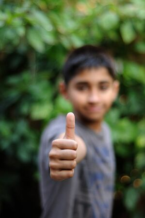 an handsome indian kid showing thumbs up for success photo