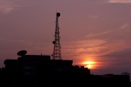 A telecom tower against a tropical sunset. Modern versus nature photo