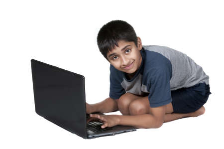 An handsome Indian kid having fun with laptop photo