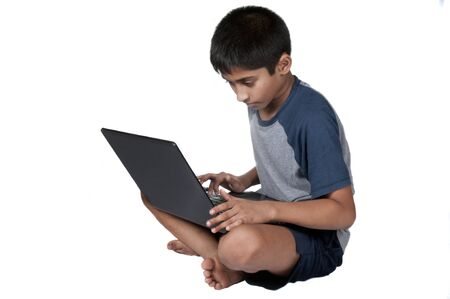 An handsome Indian kid having fun with laptop Фото со стока