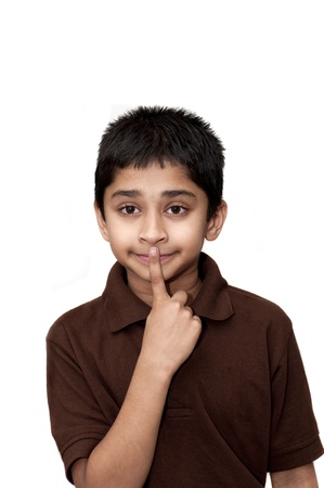 An handsome young Indian kid with finger on lips