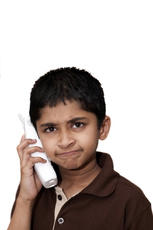 An angry Indian kid talking on a cordless phone photo