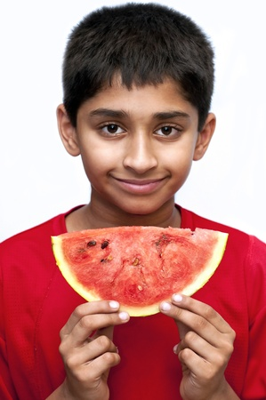 an handsome indian kid eating fresh watermelon