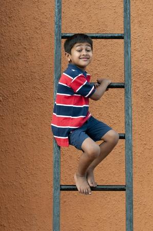 ni�o escalando: Un chico guapo indio jugando en la escalera Foto de archivo