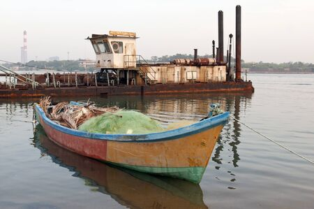 An old deserted boat tied to the pier at a local fishing harbor photo