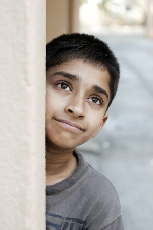 A handsome young Indian boy smiling outdoors photo