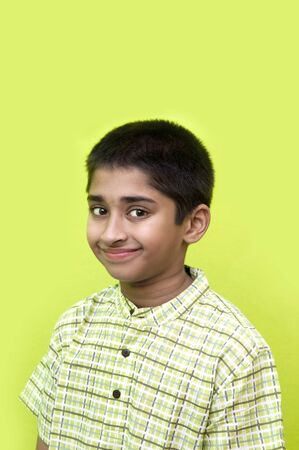 An handsome Indian kid smiling nicely for you photo