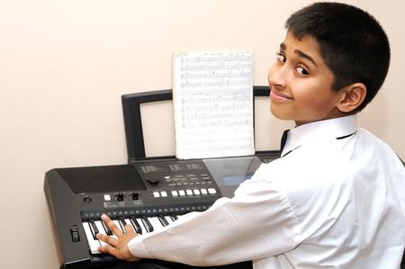 Een knappe Indiase jongen leren muziek met een elektrische piano