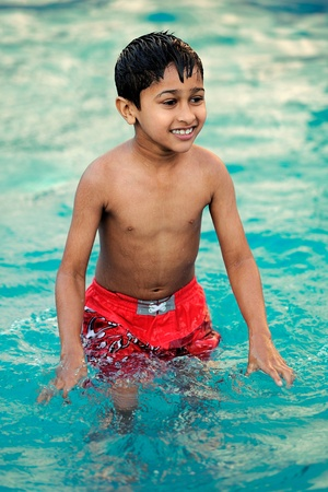 an handsome young indian kid swimming in the pool