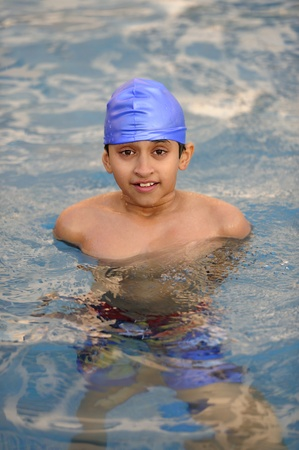 indian boy: an handsome young indian kid swimming in the pool