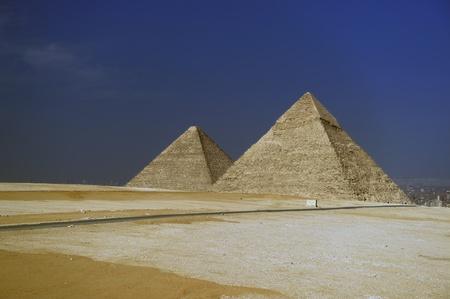 ラクダの行すべてカイロ、エジプトのギザのピラミッドの前に観光客を輸送します。