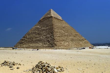 ラクダの行輸送すべてエジプトのカイロでギザのピラミッドの前で観光客 写真素材