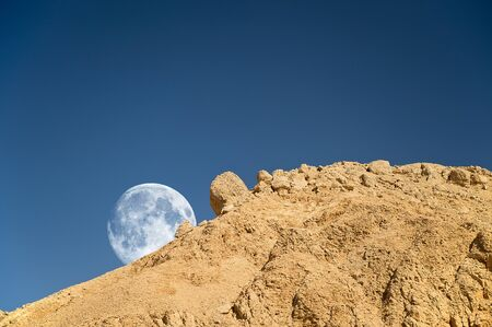 dream land: Full moon setting over the rocky desert in Egypt Stock Photo