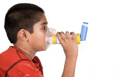 asthmatic: Close up image of a cute little boy using inhaler for asthma. White background