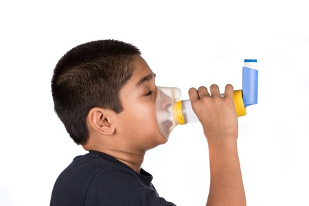 Close up image of a cute little boy using inhaler for asthma. White background