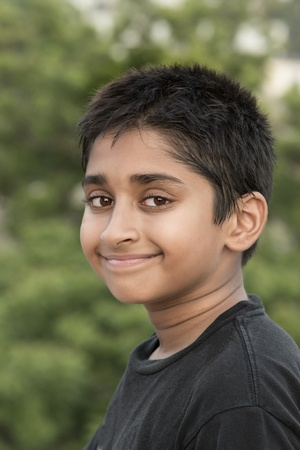 Handsome Indian boy standing outdoor smiling photo