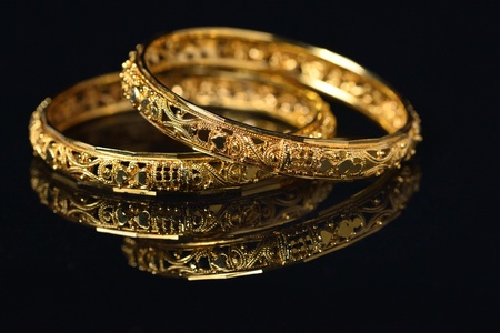 Beautiful golden bangles isolated on black backround photo
