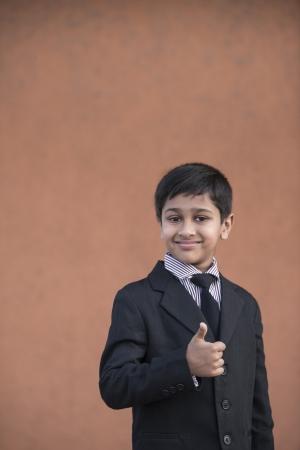formalwear: Portrait of a Handsome Little Boy in a Business Suit