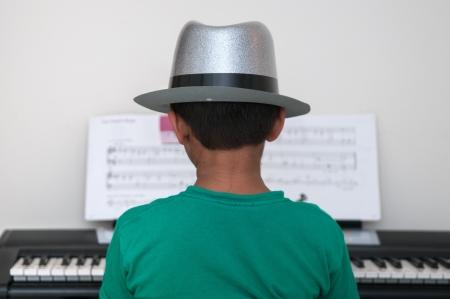 tocando piano: Un niño asiático tocando en el piano