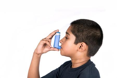 asthme: Gros plan image d'un petit gar�on mignon utilisant l'inhalateur pour l'asthme. Fond blanc