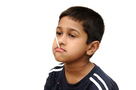 banter: an handsome Indian kid having dun savoring a lollypop Stock Photo