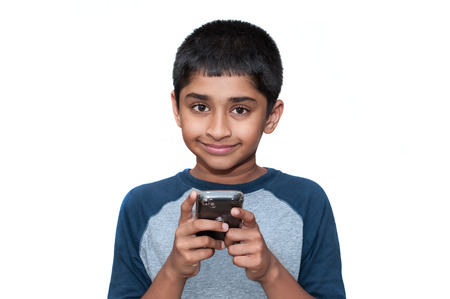 An handsome indian kid playing games with the mobile phone photo