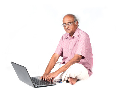 an old Indian man surfing the net after retirement Stock Photo - 24293359
