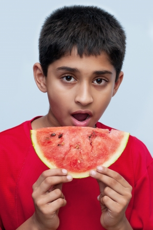 an handsome indian kid savoring a watermelon, a healthy diet 版權商用圖片