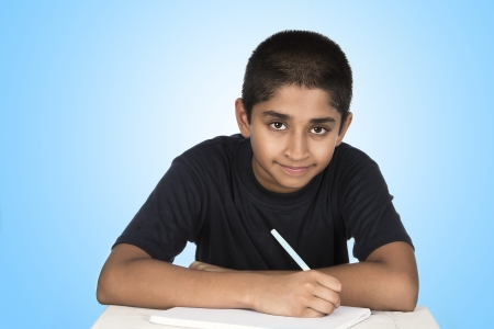An handsome Indian kid doing his homework diligently photo