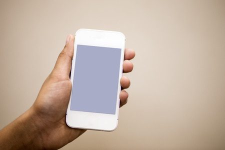 mobile communication: closeup photo of a hand holding cell phone  Stock Photo