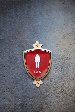 white bathroom: a men restroom sign on a concrete wall