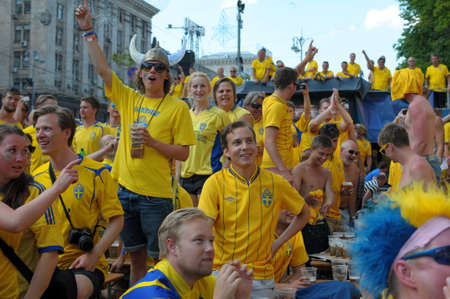 KIEV, UKRAINE - JUNE 19: Swedish football fans relax in the official fan zone of EURO-2012 in the center of Kiev, June 2012. EURO 2012 is a European football championship held by UEFA.