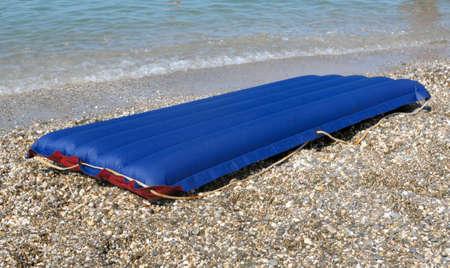 blue inflatable raft on the sand sea beach photo