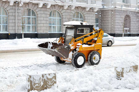 yellow tractor cleaning the snow on a street photo