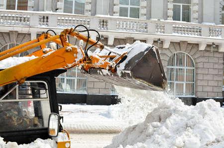 trator amarelo limpar a neve em uma rua Banco de Imagens