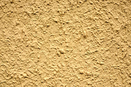 stucco wall: A yellow stucco wall useful for backgrounds or textures