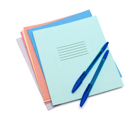 exercise books and pens on a white background photo